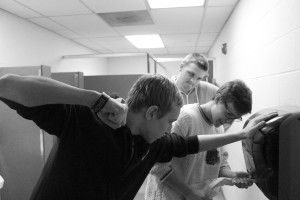 Sophomores Carter Kinstler, Joe Reinhardt and Jeremy Spriggs attempt to obtain paper towels from a Kimberly-Clark paper towel dispenser to dry their hands in the men's bathroom.Photo by Austen Klein