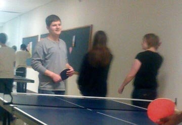 Anthony Peccola, sophomore, begins a match at ping pong club.  (Photo by Linda Coleman)
