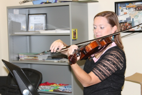 The new orchestra teacher, Lea Poe, practices her violin in her office after classes. (Photo by Alex Ring)