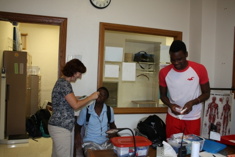 Senior Cedric Spencer gets his temperature taken with senior Zach Dixon by Nurse Rachel Huertas in her office. (Photo by Irene Ryan)