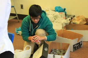 Senior Justin Saelee organizes cans for Interact Club's canned food drive. (Photo by Jack Killeen)