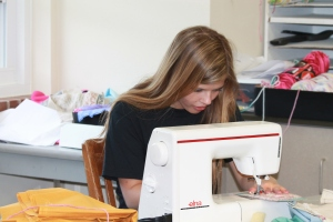 Junior Kasey Gall sews together pieced of fabric for Pookie Dolls. (Photo by Bret Waelterman)