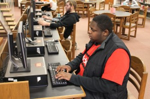 Junior Edward Flynn types on the keyboard during lunch in the library. Flynn must be knowledgeable with editing software in order to create his videos.