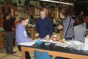 Juniors Haley Tritschler, Dean Krueger and Hannah Fettig work on a physics lab before school on Dec. 12.
