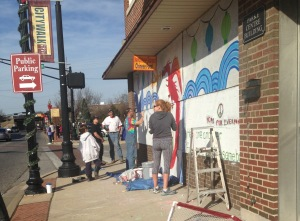 Volunteers paint a dragon on the board of a Chinese restaurant. (Photo by Irene Ryan)