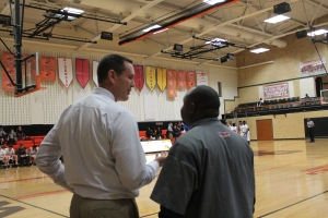 """Activities director Jerry Collins talks with Coach Dwayne Kirksey during the men's Varsity basketball game against Parkway North on Jan. 20. Webster won 85-30. """"I basically try to handle as much as the extra stuff as possible so coaches can focus on coaching,"""" Collins said. Photo by Caroline Fellows"""