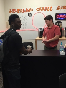 Senior Anthony Washington buys a cup of hot chocolate before school from senior Anthony Peccola at the Statesmen Coffee Shop.