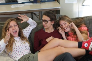 Seniors Anna Rosin, Katie Flood and Sydney Garland relax on Eric Dunn's classroom couch before school starts. Photo by Alex Ring