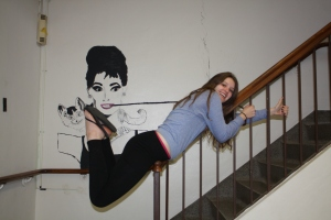 Senior Rachel Reilly chills on a stair case near the Little Theater next to actress and humanitarian Audrey Hepburn.  Photo by Phoebe Mussman