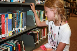 Julia Fowler examines the books in the high school library.