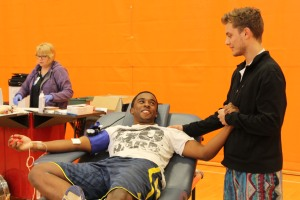 Photo By Kadifa Tabakovic Senior Corey Dunlap calms senior Bryce McLean while he is giving blood at the annual NHS blood drive on Nov. 16.
