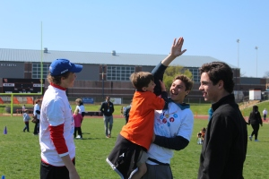 Juniors Brendan Riganti, John Moorehouse and Ryne Dobson play with one of the Special Olympic athletes during activity Day on April 5. Photo by Page Kimzey