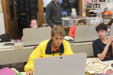 """Editor in Chief Jack Killeen works hard to get his story done for the quickly approaching deadline. Junior Sports Editor Bennett Durando looks over the man's shoulder, privately thinking, """"What a legend."""" (Photo by Jack Killeen.)"""