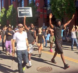 Protesters march by Busch Stadium and Ballpark Village in downtown Saint Louis. Photo by Andy Kimball