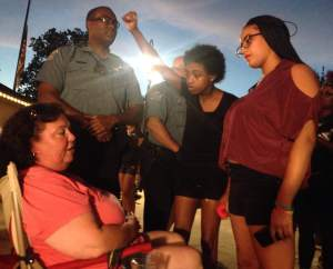 Two protesters argue with a concert viewer at the Victorian Plaza in Ferguson in July 8. Photo by Andy Kimball