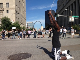 "While downtown protesters form a circle and chant, ""Hands up, don't shoot,"" a lone protester kneels in the middle with his eyes closed. Photo by Bennett Durando"