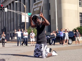 """While downtown protesters form a circle and chant, """"Hands up, don't shoot,"""" a lone protester kneels in the middle with his eyes closed. Photo by Bennett Durando"""