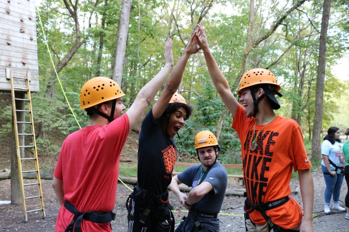 Seniors Noah Dent, Che Sanchez, David Kern and Noah Burgess high five before attempting the climbing the wall at Camp Wyman on Monday, Oct. 5.
