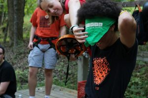 Senior Che Sanchez ties a bandanna around his neck before putting on a helmet at the climbing wall.