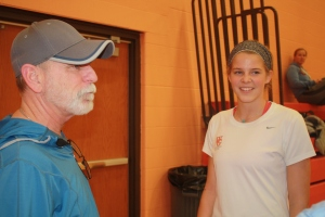New soccer coach Thom Champion consults with senior player Megan McClure at an evening practice.