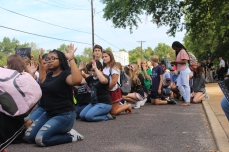 There was a moment of silence during which the students knelt on the ground with their hands up in front of the gate facing the police officers. Photo by Ashli Wagner