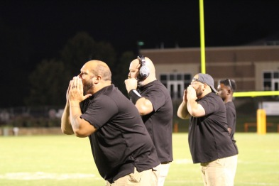 Coaches James LeMay, Matthew Doner and Desmond Reichold yell plays from the sidelines.